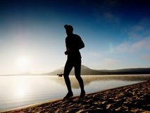 Funzionamento dell'uomo al tempo di penombra della spiaggia Funzionamento dell'atleta del corridore alla spiaggia Siluetta di for Fotografia Stock Libera da Diritti