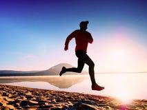 Funzionamento dell'uomo al tempo di penombra della spiaggia Funzionamento dell'atleta del corridore alla spiaggia Siluetta di for Immagine Stock Libera da Diritti
