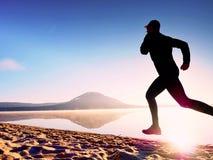 Funzionamento dell'uomo al tempo di penombra della spiaggia Funzionamento dell'atleta del corridore alla spiaggia Siluetta di for Immagine Stock