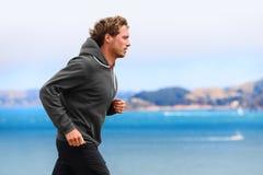 Funzionamento dell'uomo dell'atleta nella maglia con cappuccio della maglietta felpata Immagini Stock Libere da Diritti