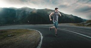 Funzionamento dell'uomo di forma fisica sulla strada principale intorno alle montagne Immagine Stock