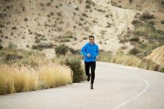Funzionamento dell'uomo di sport sul paesaggio asciutto del deserto nello stile di vita sano di forma fisica Immagini Stock