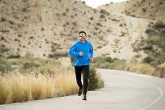 Funzionamento dell'uomo di sport sul paesaggio asciutto del deserto nello stile di vita sano di forma fisica Immagine Stock
