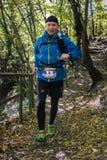 Funzionamento dell'uomo invecchiato mezzo lungo il sentiero nel bosco Fotografie Stock