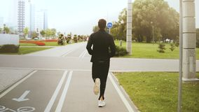 funzionamento dell'uomo 4K lungo una strada del parco della città Vista posteriore Corridore di forma fisica in abiti sportivi ne stock footage