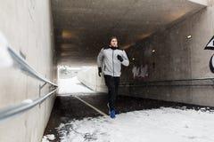 Funzionamento dell'uomo lungo il tunnel del sottopassaggio nell'inverno Immagine Stock