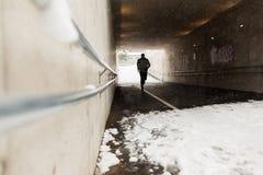 Funzionamento dell'uomo lungo il tunnel del sottopassaggio nell'inverno Fotografia Stock