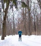 Funzionamento dell'uomo nella foresta della neve nell'inverno fotografia stock libera da diritti