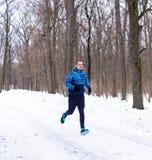 Funzionamento dell'uomo nella foresta di inverno con molta neve immagine stock