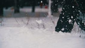 Funzionamento dell'uomo nella neve profonda nella foresta di inverno al giorno di Snowy Movimento lento stock footage