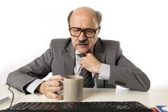 Funzionamento dell'uomo 60s di affari sollecitato e frustrato allo scrittorio del computer portatile del computer di ufficio che  immagini stock