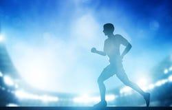Funzionamento dell'uomo sullo stadio nelle luci notturne Funzionamento di atletica Fotografia Stock