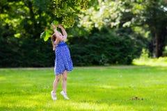 Funzionamento della bambina nel parco soleggiato Immagini Stock