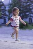 Funzionamento della bambina Ragazza felice 2-3-4 anni con le trecce che corrono giù la strada nel parco Fotografia Stock