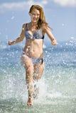 Funzionamento della donna alla spiaggia Immagine Stock