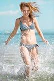 Funzionamento della donna alla spiaggia Fotografie Stock