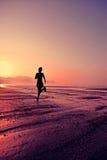 Funzionamento della donna alla spiaggia di alba Immagine Stock
