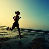 Funzionamento della donna alla spiaggia di alba Immagini Stock