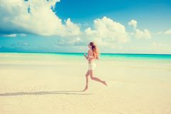 Funzionamento della donna che pareggia durante l'allenamento all'aperto sulla spiaggia Immagini Stock