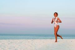 Funzionamento della donna del corridore nella spiaggia al tramonto Fotografie Stock