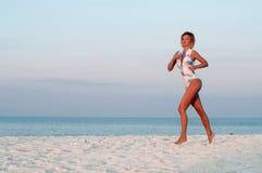 Funzionamento della donna del corridore nella spiaggia al tramonto Fotografia Stock Libera da Diritti