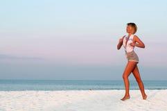 Funzionamento della donna del corridore nella spiaggia al tramonto Fotografie Stock Libere da Diritti