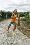 Funzionamento della donna dell'atleta Immagini Stock