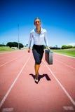Funzionamento della donna di affari su una pista corrente Fotografie Stock Libere da Diritti