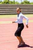 Funzionamento della donna di affari su una pista corrente Fotografie Stock
