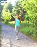 Funzionamento della donna di forma fisica nel parco, nell'allenamento femminile del corridore, nello sport e nello stile di vita  Fotografia Stock