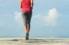 Funzionamento della donna di forma fisica nella costa ad alba Fotografia Stock