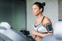 Funzionamento della donna di forma fisica sulla pedana mobile che ascolta la musica durante il Wor Fotografia Stock Libera da Diritti