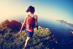 Funzionamento della donna di forma fisica sulla traccia di montagna della spiaggia Immagine Stock