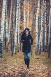 Funzionamento della donna di modo nel parco di autunno Fotografie Stock Libere da Diritti