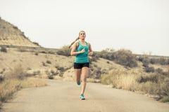 Funzionamento della donna di sport sulla strada sporca dell'asfalto con il fondo asciutto del paesaggio del deserto che si prepar Fotografia Stock