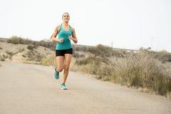 Funzionamento della donna di sport sulla strada sporca dell'asfalto con il fondo asciutto del paesaggio del deserto che si prepar Immagine Stock