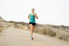 Funzionamento della donna di sport sulla strada sporca dell'asfalto con il fondo asciutto del paesaggio del deserto che si prepar Fotografie Stock