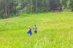 Funzionamento della donna e del giovane sul prato della campagna con erba verde Immagine Stock