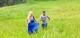 Funzionamento della donna e del giovane sul prato della campagna con erba verde Immagini Stock