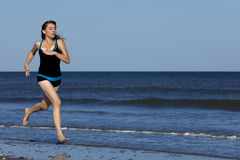 Funzionamento della donna sulla spiaggia a piedi nudi Fotografie Stock Libere da Diritti