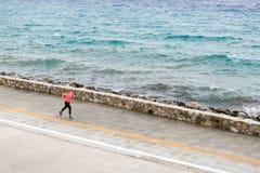 Funzionamento della donna sulla via della città alla spiaggia Immagine Stock Libera da Diritti
