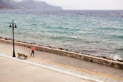 Funzionamento della donna sulla via della città alla spiaggia Fotografie Stock Libere da Diritti