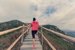 Funzionamento della donna sulle scale della montagna Fotografia Stock