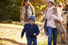 Funzionamento della famiglia lungo il percorso attraverso Autumn Countryside Immagini Stock