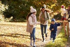 Funzionamento della famiglia lungo il percorso attraverso Autumn Countryside Immagine Stock