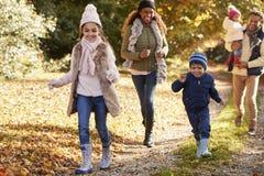 Funzionamento della famiglia lungo il percorso attraverso Autumn Countryside Fotografia Stock