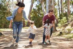 Funzionamento della famiglia lungo il percorso attraverso Forest Together Immagini Stock