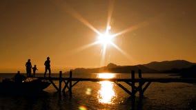 Funzionamento della famiglia sul ponte al tramonto stock footage