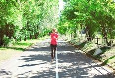 Funzionamento della giovane donna di forma fisica nel parco di estate, nell'allenamento femminile del corridore - sport e nello s Immagine Stock Libera da Diritti