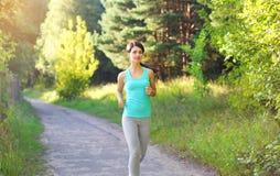 Funzionamento della giovane donna di forma fisica nel parco, nell'allenamento femminile del corridore, nello sport e nello stile  Immagini Stock Libere da Diritti